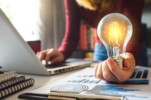 Image of woman at computer holding a lit lightbulb
